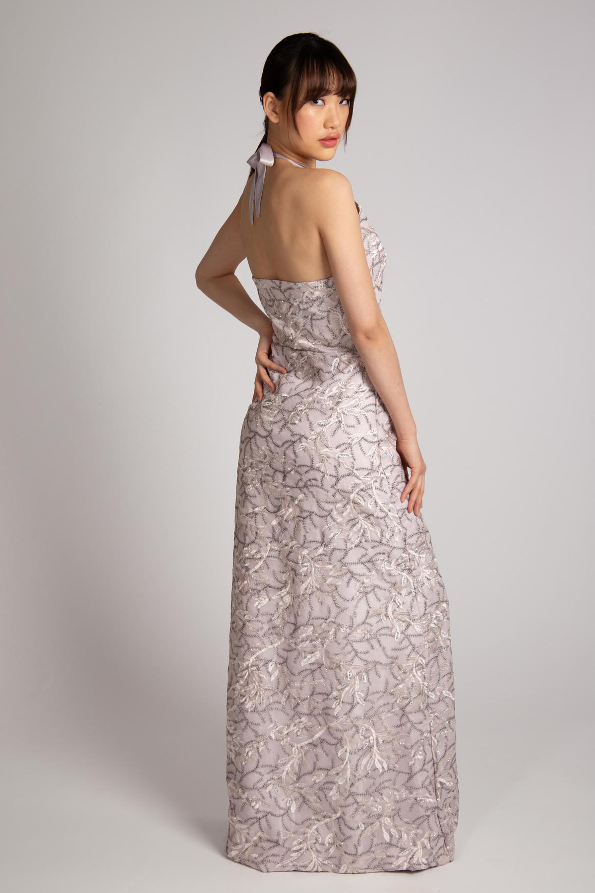 Hongman Li models a silver violet evening gown with low cut back made of tulle with embroidery.